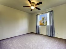 Empty room with curtains, grey carpet  and fan. Stock Photos