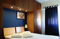 Empty Bed Room with Dark Navy Blue Wall and Wooden Wardrobe. Modern room with one wall painted in dark navy blue, wooden bed and wardrobes. White cushions and Royalty Free Stock Image