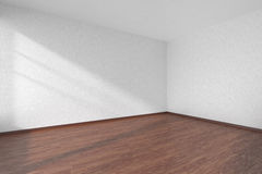 Empty room with dark parquet floor and textured white walls Royalty Free Stock Images
