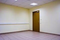 Empty room door. Corner of empty office room with floor of stones, ceiling, door, lamps and yellow walls Royalty Free Stock Photos