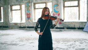 Empty room with a female violinist playing the instrument. 4K stock video footage