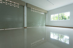 Empty room in house residential building with aluminium roller. Shutter door and window glass sliding and white flooring tile Royalty Free Stock Photo