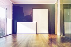 Empty blue room, two posters toned. Empty room interior with blaue walls, a wooden floor, panoramic windows and two framed posters. 3d rendering mock up Royalty Free Stock Images