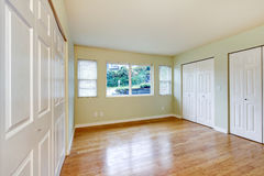 Empty room interior with hardwood floor and three closets. Stock Photography