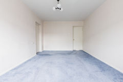 Empty Room. Interior photo of the empty living room with white walls and gray carpet Stock Image