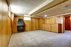 Empty room interior with wooden panel trim walls and fireplace. Stock Photo