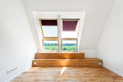 Empty Room of New Home with Wood Floors, White Walls and Bright Skylights. Stock Photo