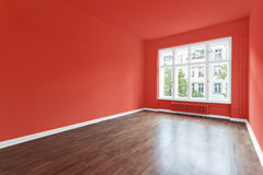 Empty room - newly renovated room. Empty room with red walls and wooden floor - newly renovated room with red painted walls stock photography