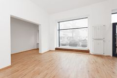 Empty room newly renovated - store / shop with wooden floor and Stock Photos