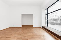 Empty room newly renovated - store / shop with wooden floor and. Renovated room with shopping window - empty store / shop with wooden floor and white walls royalty free stock images