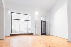 Empty room newly renovated - store / shop with wooden floor and. Renovated room with shopping window - empty store / shop with wooden floor and white walls stock photography