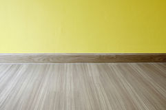 Empty room with oak wood laminate flooring and newly painted yel Stock Images