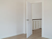 Empty room with open door and white interior wall background. Empty room with open door and white wall background royalty free stock images