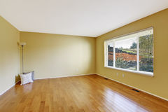 Empty room in soft ivory with new hardwood floor. And window. Decorated with lamp and pillows Stock Photos
