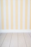 Empty room with striped wall. Empty room background with striped yellow wallpaper a wooden floor and a plant Royalty Free Stock Photos