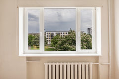 Empty Room With View. Interior of an empty room with large window and blooming horse chestnut tree behind the window Royalty Free Stock Photo
