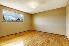 Empty room with window and hardwood floor. Empty bedroom in soft ivory with one window and hardwood floor Royalty Free Stock Photography