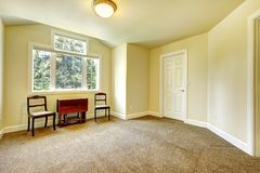 Empty room with yellow walls and brown carpet. Royalty Free Stock Photos