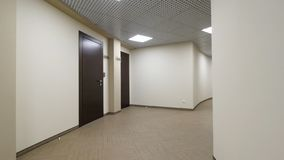 Empty, round corridor with light beige walls and closed, dark brown doors. Closed doors along a lighted corridor in the stock photo