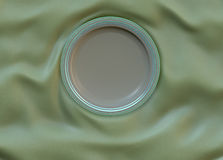 Empty round glazed plate with simple shiny frame on folded silk cloth. Royalty Free Stock Image