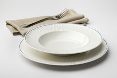 Empty round white plate and bowl with napkin and fork Stock Photography