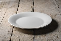 Empty white round plate on rough wooden table. Empty round white plate with smooth edge on rough wooden table Stock Photo