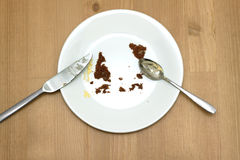 Empty round white plate with traces of eaten cake closeup Stock Images