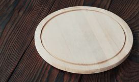 Empty round wooden board for cutting on a wooden background. Background for product montage. empty round wooden board for cutting on a wooden background Royalty Free Stock Photos