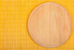 Empty round wooden board with tablecloth. Background for product montage. Empty round wooden board with tablecloth Royalty Free Stock Images
