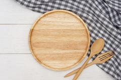 Empty round wooden plate with spoon, fork and grey gingham tablecloth on white wooden table. royalty free stock photo