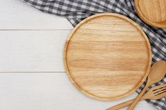 Empty round wooden plate with spoon, fork and grey gingham tablecloth on white wooden table. stock photo
