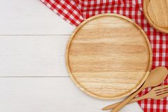 Empty round wooden plate with spoon, fork and red gingham tablecloth on white wooden table. royalty free stock images