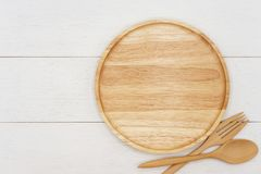 Empty round wooden plate with spoon and fork on white wooden table. royalty free stock photography