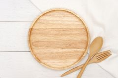Empty round wooden plate with spoon, fork and white tablecloth on white wooden table. stock photography