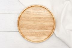 Empty round wooden plate with white tablecloth on white wooden table. royalty free stock image