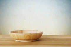 Empty round wooden plate on wood table background, food display Royalty Free Stock Images