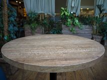 Empty round wooden table in a restaurant on the background of green plants royalty free stock photos