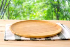 Empty round wooden tray and napery on table over blur tree backg Royalty Free Stock Photo