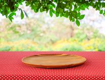 Empty round wooden tray on red polka dot tablecloth over blur tr Royalty Free Stock Photos