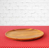 Empty round wooden tray on red polka dot tablecloth over white b Stock Photo