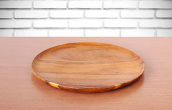 Empty round wooden tray on table over white brick wall background. For product display montage royalty free stock images