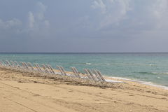 Empty row of beach chairs on shoreline Royalty Free Stock Image