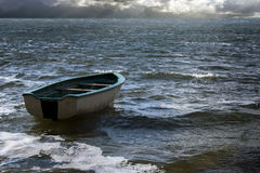 Empty rowboat floats lonely on the sea waves to the clouds at th Stock Photography
