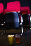 Empty rows of red seats with pop corn and drink on the floor Stock Photo