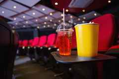 Empty rows of red seats with pop corn and drink on the floor Stock Photos