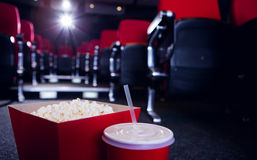 Empty rows of red seats with pop corn and drink on the floor Royalty Free Stock Photography