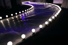 Empty Runway Fashion Show with Ball glowing lighting along walk way Royalty Free Stock Images