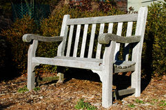 Empty Rustic Bench. An empty wooden park bench sits in the garden in the winter Stock Image