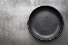Empty Rustic Black Plate over Slate Stock Image