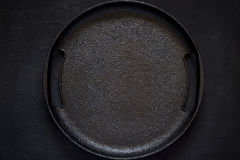 Empty rustic cast iron plate On a black background. Top view wit Royalty Free Stock Images